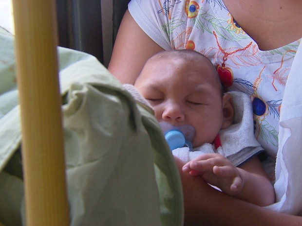 Jaqueline pega três ônibus para levar o filho Daniel, de quatro meses, para consultas médicas e fisioterapia (Foto: Reprodução / TV Globo)