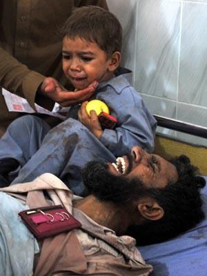 Menino chora ao lado do pai, ferido no atentado nesta quarta-feira (19) em Peshawar, no Paquistão (Foto: AFP)