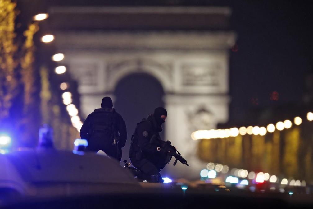 Policiais mascarados vigiam avenida Champs-Élysées de cima de um veículo (Foto: REUTERS/Christian Hartmann )