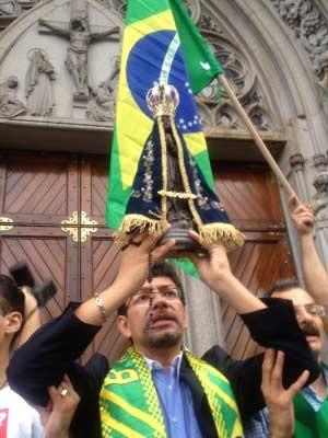 Integrante da Marcha ergue imagem de Nossa Senhora Aparecida na frente da Catedral da Sé (Foto: G1)