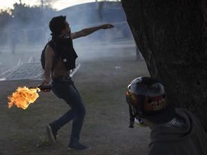Manifestante atira coquetel molotov contra a polícia em Belo Horizonte (Foto: Felipe Dana/AP)