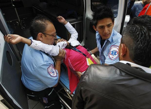 Paramédicos ajudam uma mulher que desmaiou durante retirada de trabalhadores de um prédio na Cidade do México (Foto: Bernardo Montoya/Reuters)