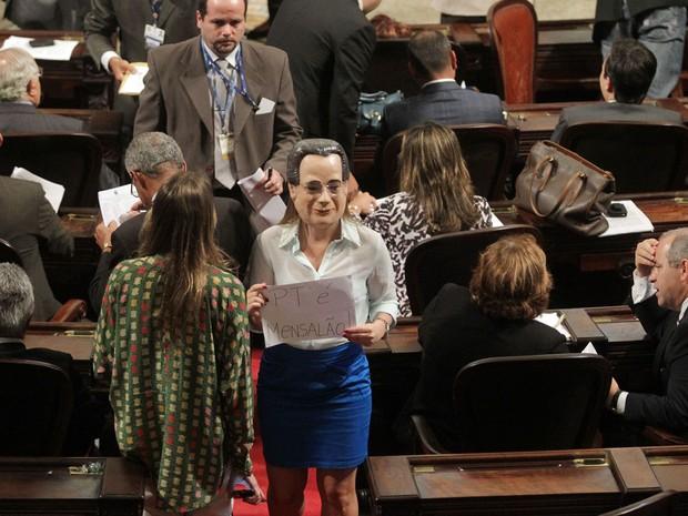 """A deputada estadual Clarissa Garotinho (PR-RJ) usa máscara do ex- ministro José Dirceu e exibe um cartaz com a frase """"PT é Mensalão"""" durante a votação que pretende proibir o uso de máscaras em manifestações. (Foto: Marcos de Paula/Estadão Conteúdo)"""