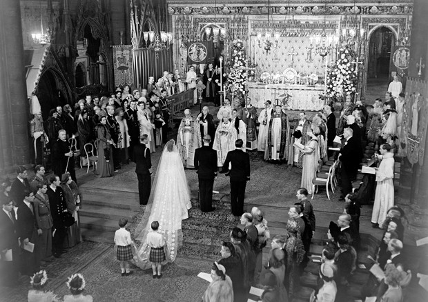 The scene at the altar steps during the Royal Wedding Ceremony in Westminster Abbey. H.M the King stands to the left of the bride; on the bridegroom's right is the groomsman, the Marques of Milford Haven. The bride's train is held by two pages T.R.H Princ (Foto: PA Archive/PA Images)