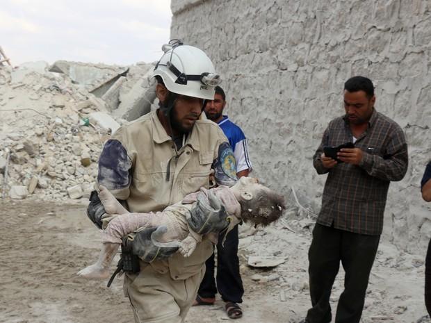 Um voluntário de defesa civil síria carrega o corpo de criança que morreu após um ataque no bairro de Tariq al-Bab, no norte da cidade de Aleppo, no dia 27 de maio (Foto: Thaer Mohammed/AFP)