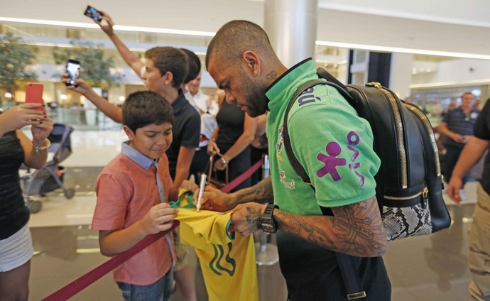 Daniel Alves dá autógrafo na chegada da seleção brasileira no Paraguai (Foto: Rafael Ribeiro/CBF)