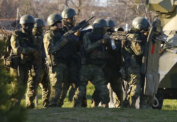 Homens armados que estariam a serviço da Rússia se protegem atrás de veículo blindado enquanto tomavam a base ucraniana de Belbek neste sábado (22) (Foto: Shamil Zhumatov/Reuters)