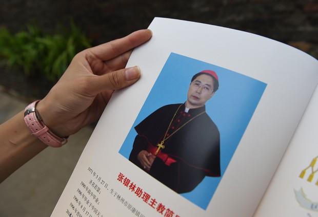 Fiel católico mostra livro com foto do novo bispo Joseph Zhang Yilin, ordenado nesta terça-feira (4), em Anyang, na China (Foto: Greg Baker / AFP)