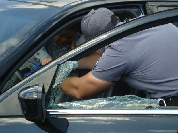 Bombeiros quebraram um dos vidros do veículo para retirar a criança que estava chorando. (Foto: Gláucia Souza / G1)