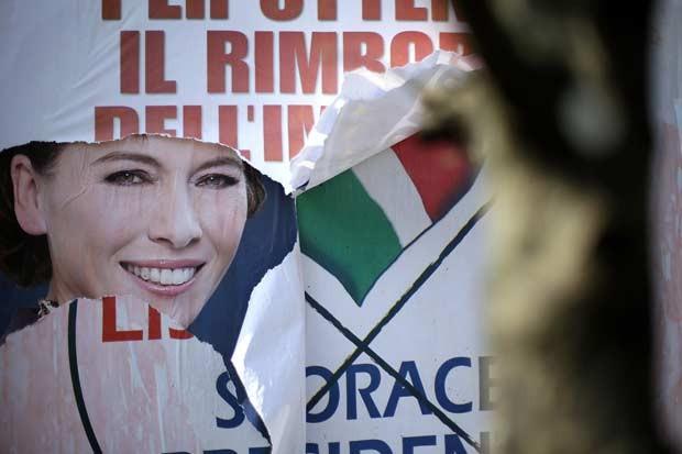 Cartazes remanescentes da campanha eleitoral tomam muro em Roma nesta terça-feira (26) (Foto: AFP)
