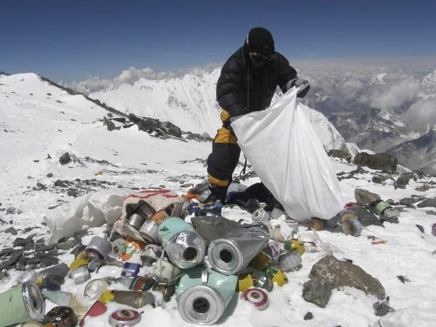 Imagem de maio de 2010 mostra guia nepalês recolhendo lixo a 8 mil metros de altura, no cume do Monte Everest (Foto: Namgyal Sherpa/AFP)
