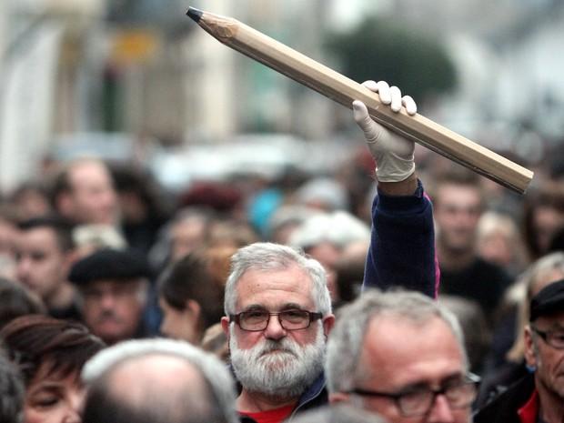 Um homem segura um lápis gigante durante uma marcha em Tarbes, no sul da França, em homenagem às 12 pessoas mortas por dois atiradores na redação da revista 'Charlie Hebdo' nesta quarta-feira (7) em Paris (Foto: Laurent Dard/AFP)