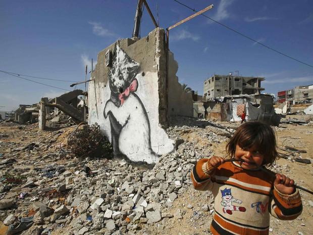 Menina palestina brinca em frente a um mural cuja autoria é atribuída ao artista de rua britânico Banksy, em Biet Hanoun, no norte da Faixa de Gaza. A obra aparece entre outras em uma sessão de fotos divulgada no site de Banksy (banksy.co.uk) (Foto: Suhaib Salem/Reuters)
