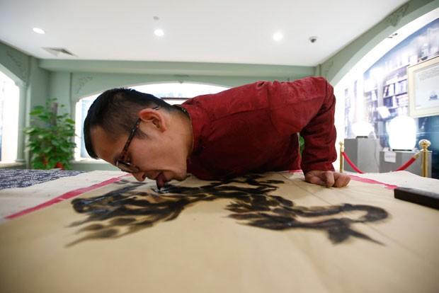 Han ganhou notoriedade no país asiático ao pintar suas obras usando a língua como pincel (Foto: Aly Song/Reuters)