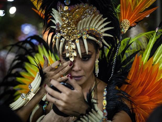 Carol Nakamura se protege da chuva e retoca a maquiagem sob a cobertura de uma lanchonete na concentração da Sapucaí (Foto: Fábio Tito/G1)
