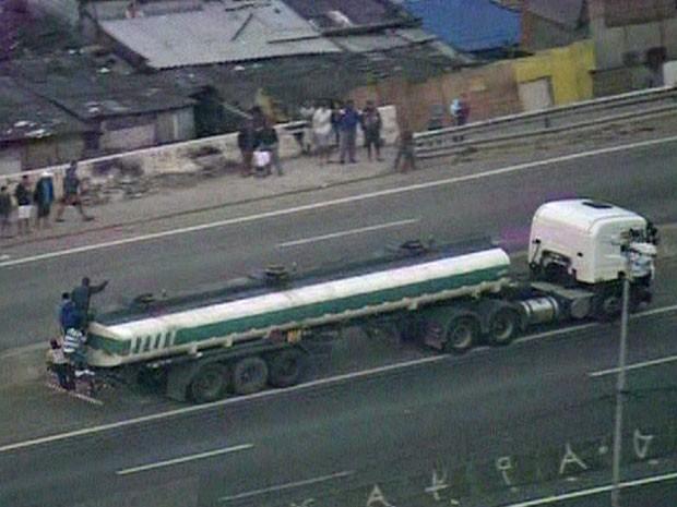 Manifestantes sobre caminhão-tanque na Rodovia Fernão Dias (Foto: Reprodução/TV Globo)