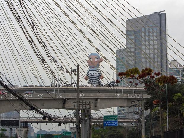 Um boneco inflável gigante fazendo alusão ao ex-presidente Luiz Inácio Lula da Silva em trajes de presidiário é visto em forma de protesto sobre a ponte estaiada Octavio Frias de Oliveira, na Avenida Jornalista Roberto Marinho, Zona Sul de São Paulo (Foto: Marco Ambrosio/Estadão Conteúdo)