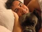 Sem camisa, André Marques posa deitado na cama
