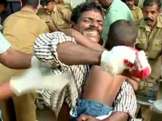 Um homem ferido leva seu filho antes de receber atendimento médico em um hospital (Foto: ANI / via Reuters)