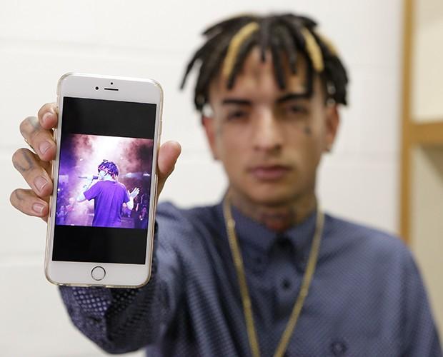 MC Guimê exibe foto que foi tirada no seu show (Foto: Artur Meninea / TV Globo)