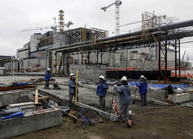 Operários trabalham no dia 23 de março perto do local onde ficava o quarto reator danificado da usina nuclear de Chernobyl, na Ucrânia (Foto: Gleb Garanich/Reuters)