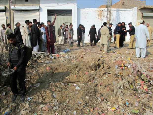 Policiais paquistaneses e muçulmanos xiitas inspecionam local da explosão de uma bomba nos arredores de Dera Ismail Khan, neste sábado (24) (Foto: AFP)