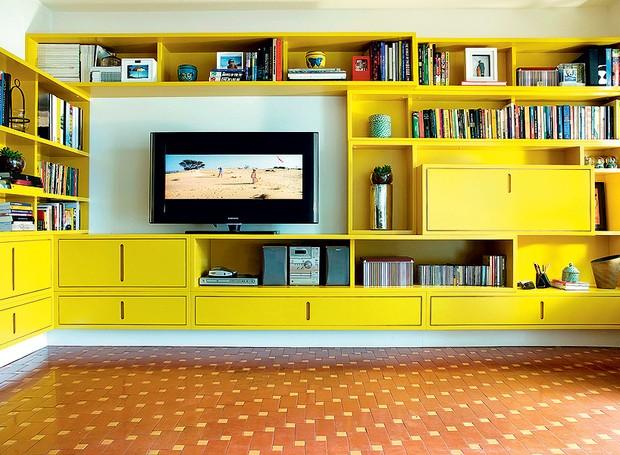 A arquiteta Cláudia Pecego projetou uma estante de MDF com acabamento em gofrato amarelo. Para amenizar o visual marcante, a profissional pediu que fossem respeitadas as linhas retas e solicitou que a base da estante fosse pintada de branco, dando a impre (Foto: Célia Weiss)