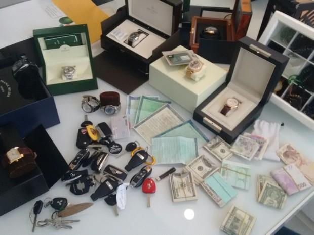 Relógios, jóias e dinheiro foram encontrados em residência de suspeitos (Foto: Divulgação / Secretaria de Segurança)