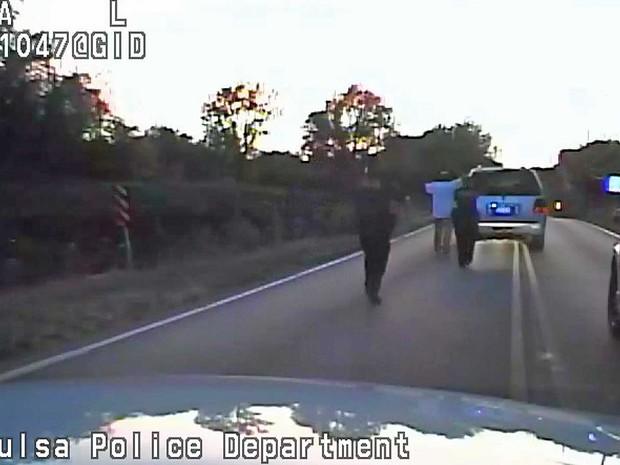 Terence Crutcher, com as mãos na cabeça, é escoltado por policiais até seu carro (Foto: Departamento de Polícia de Tulsa / via AP Photo)