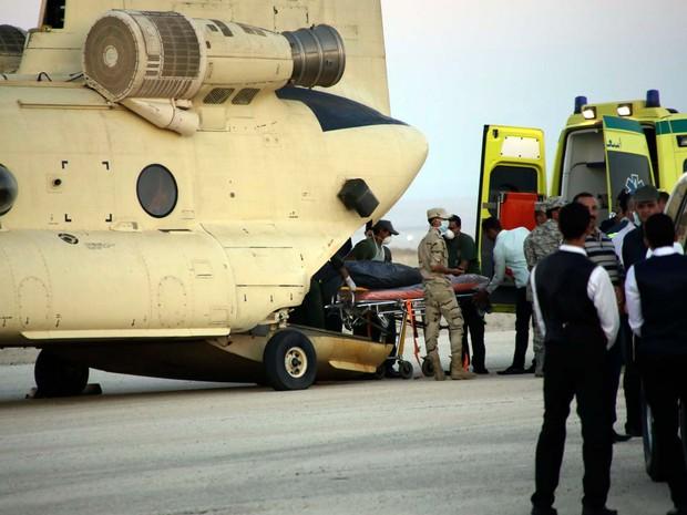 Corpo de vítima da queda do avião russo no Sinai egípcio é transportado de um helicóptero a ambulâncias no aeroporto militar de Kabrit (Foto: AP Photo/Amr Nabil)