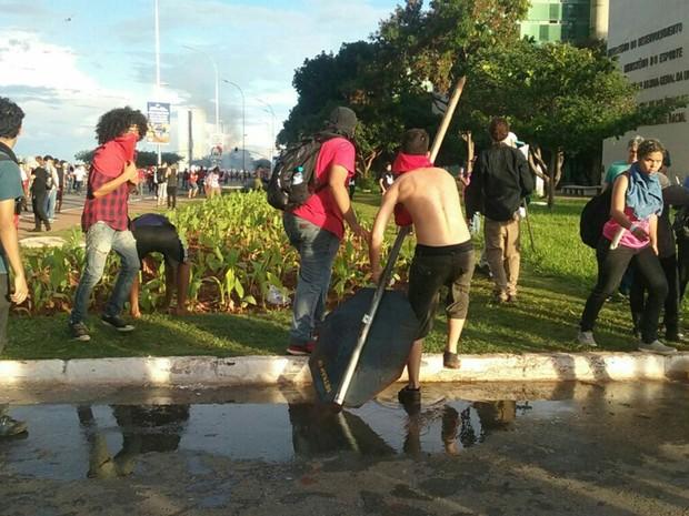 Grupo arranca placa de trânsito durante protesto em Brasília nesta terça-feira (29) contra a PEC que limita o teto de gastos (Foto: Luiza Garonce/G1)