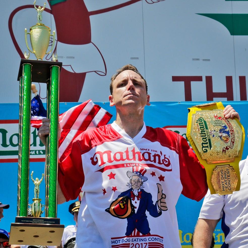 Joey Chestnut posa com o troféu e cinturão ganhos após comer 72 cachorros quentes e vencer concurso em Nova York, na terça (4) (Foto: AP Photo/Bebeto Matthews)