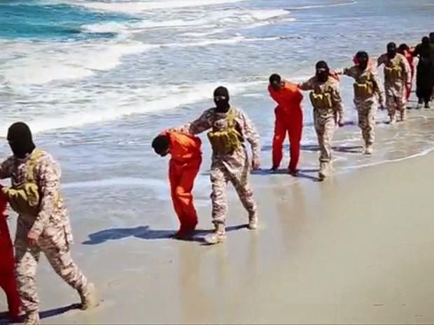 Militantes mascarados aparecem levando prisioneiros em praia (Foto: AP Photo)