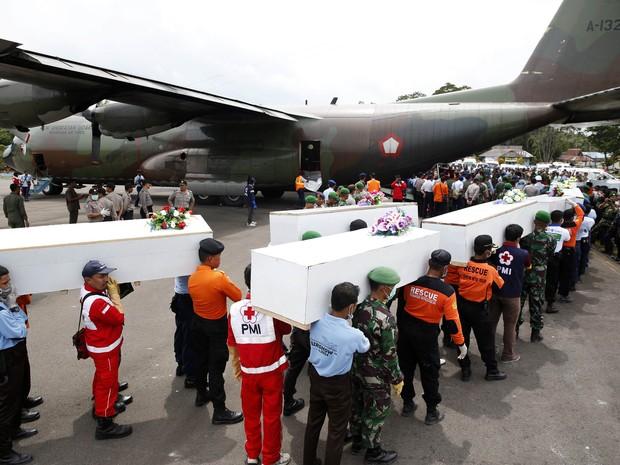 Caixões com os restos mortais dos passageiros do voo da AirAsia são transportados para Surabaya neste sábado (3) (Foto: Darren Whiteside/Reuters)