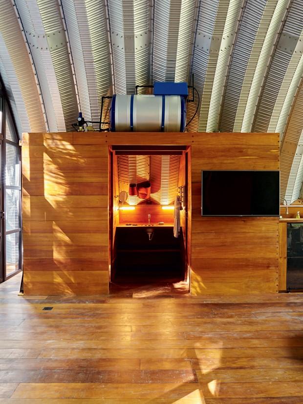 Banheiro | Em cima da caixa de madeira fica um boiler de 300 litros com água aquecida por sistema elétrico. No centro, a bancada tem pia típica de barco (Foto: Victor Affaro)