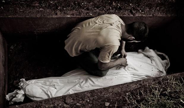 Homem ajeita o corpo de Mohamed na sepultura no cemitério islâmico de Guarulhos (Foto: Gabriel Chaim/G1)