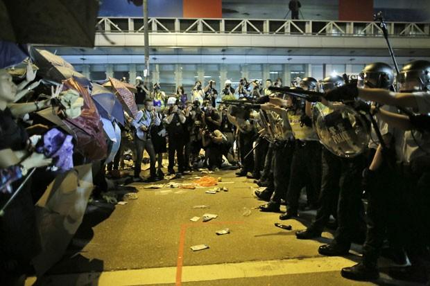 Policiais apontam armas para manifestantes durante protesto em Hong Kong, neste domingo (19). Milhares de moradores ocupam desde sábado as ruas do distrito de Mong Kok e pedem democracia (Foto: Vincent Yu/AP)