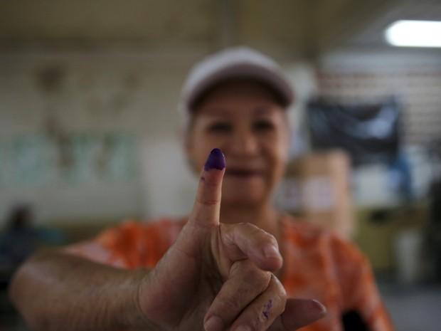 Eleitora exibe o dedo pintado após votar nas eleições parlamentares em Caracas, Venezuela, neste domingo (6) (Foto: REUTERS/Nacho Doce)