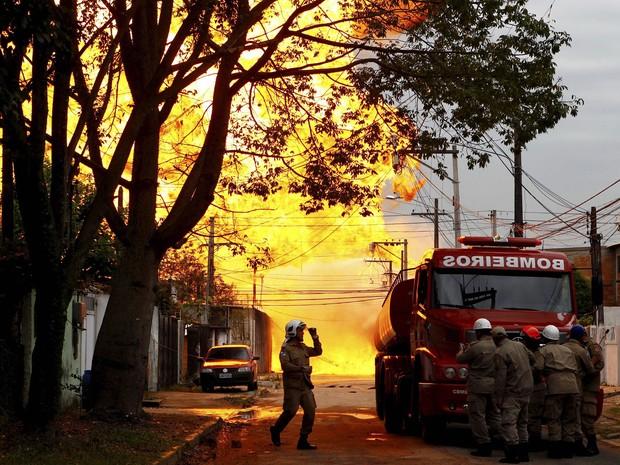 À direita, bombeiros se protegem do fogo atrás de um caminhão da corporação em Duque de Caxias (Foto: Pablo Jacob/Agência O Globo)