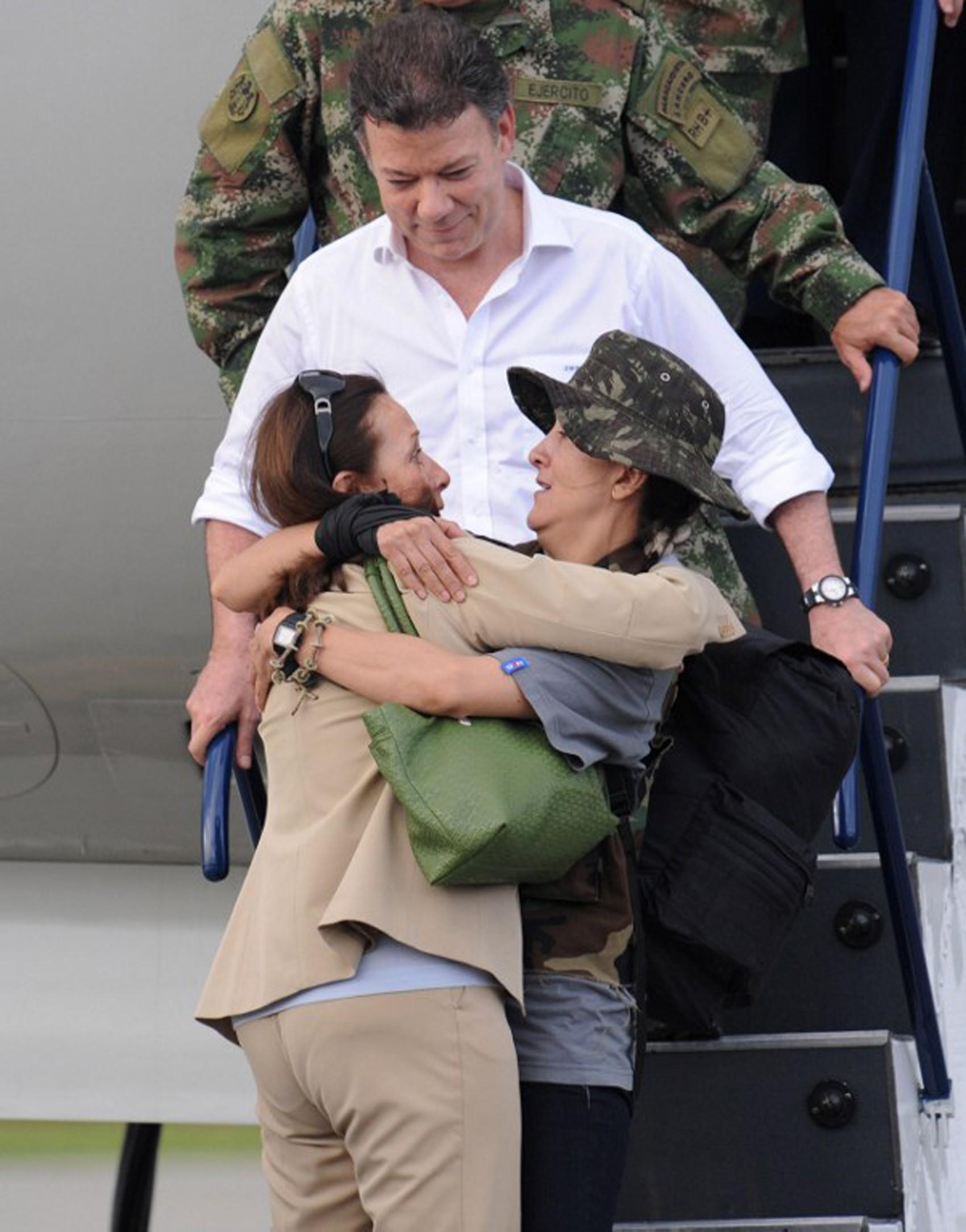 Como ministro da Defesa, Juan Manuel Santos observa a ex-refém das Farc Ingrid Betancourt abraçar a mãe dela,Yolanda Pulecio, em 2 de julho de 2008 (Foto: Rodrigo Arangua / AFP)