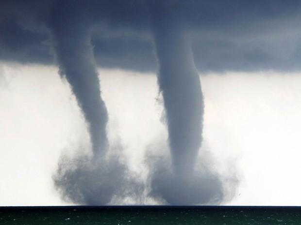 Dupla de trombas d'água é vista sobre o Lago Michigan ao sudeste de Kenosha, no estado americano de Wisconsin. O Serviço Nacional de Meteorologia em Sullivan disse que o fenômeno, que é basicamente um tornado sobre a água, ocorreu a 6,4 km de Kenosha. (Foto: Kevin Poirier/The Kenosha News,/AP)