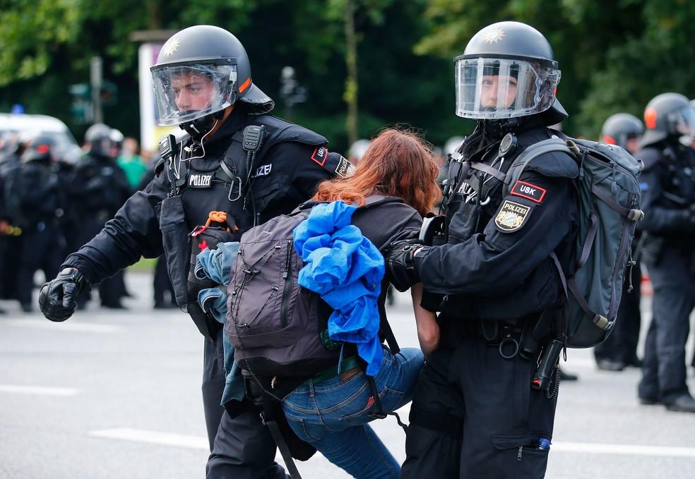 Policial retira manifestante que bloqueava rua em Hamburgo, na Alemanha, nesta sexta-feira (7) (Foto: Hannibal Hanschke/ Reuters)