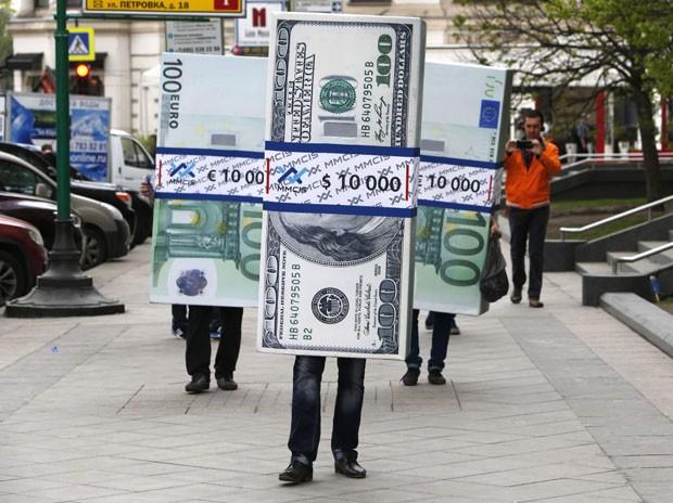 Trio de maços de dólares e euros anda pelas ruas de Moscou, na Rússia (Foto: Sergei Karpukhin/Reuters)