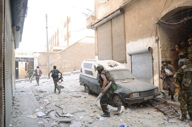Forças de Assad durante combate em Aleppo nesta quinta-feira (20) (Foto: Reuters)