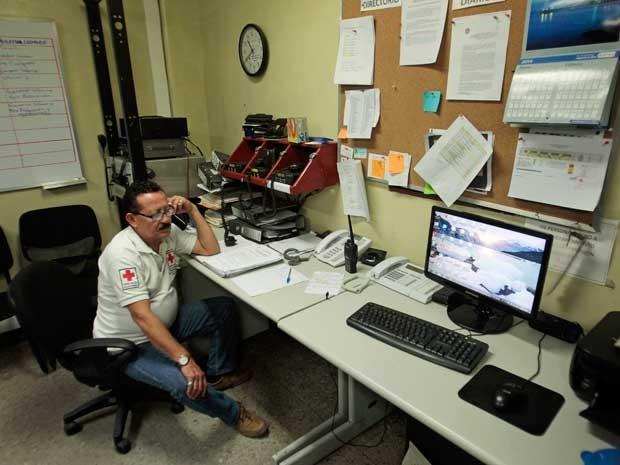 Integrante da Cruz Vermelha dá orientações por telefone após forte tremor atingir El Salvador. (Foto: Jose Cabezas / Reuters)