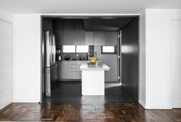 Cozinha. Concebida como um cubo escuro, tem apenas um contraste, a ilha central branca (Foto: Mariana Boro / Editora Globo)