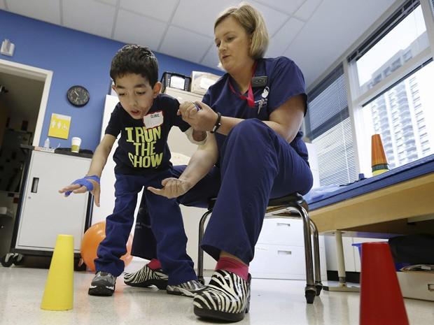 Terapeuta Katherine Hartigan trabalha com Ihor no hospital; garoto reaprendeu a andar depois de cirurgias (Foto: AP Photo/Michael Dwyer)
