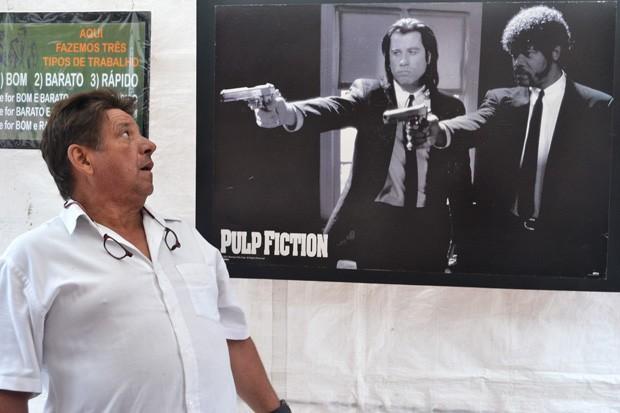 """Lojista da Liberdade interage com cartaz do filme """"Pulp Finction"""" (Foto: © Daniel Nunes Gonçalves)"""