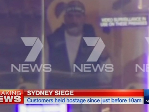 Homem com faixa na cabeça é visto dentro do café onde reféns foram feitos em Sydney, na Austrália, em imagem reproduzida de uma emissora local (Foto: Reuters/Seven Network)