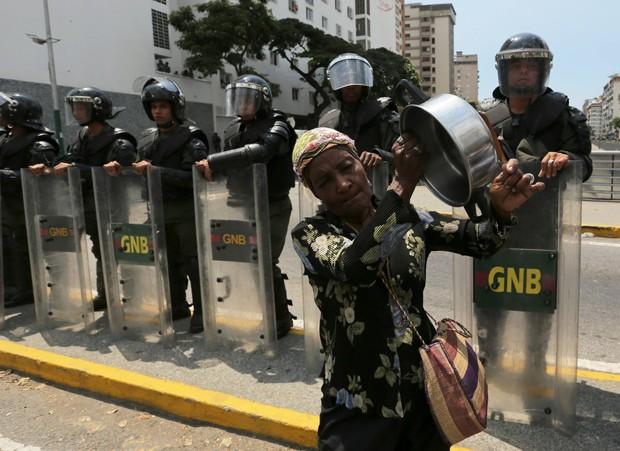 Mulher bate em panela vazia diante de membros da Guarda Nacional Bolivariana durante protesto em Caracas, na Venezuela (Foto: Fernando Llano/AP)